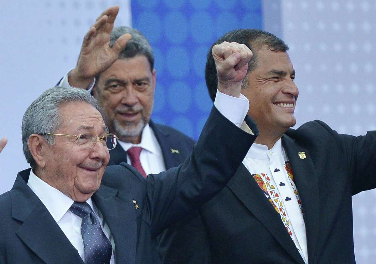 Cuba's President Raul Castro (L) raises his fist next to Ecuadorean President Rafael Correa (R) during the official family photo of the Summit of the Americas at the ATLAPA Convention Center on April 11, 2015 in Panama City. AFP PHOTO/MANDEL NGANMANDEL NGAN/AFP/Getty Images