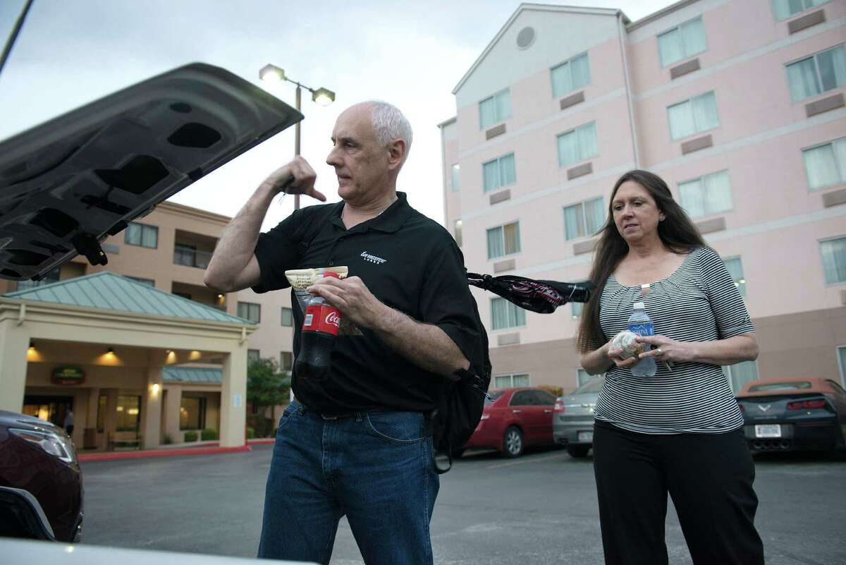 Kendell and Lenora Hodges gather their belongings from their car at a one of the hotels they've been staying in as they look for a house in San Antonio.