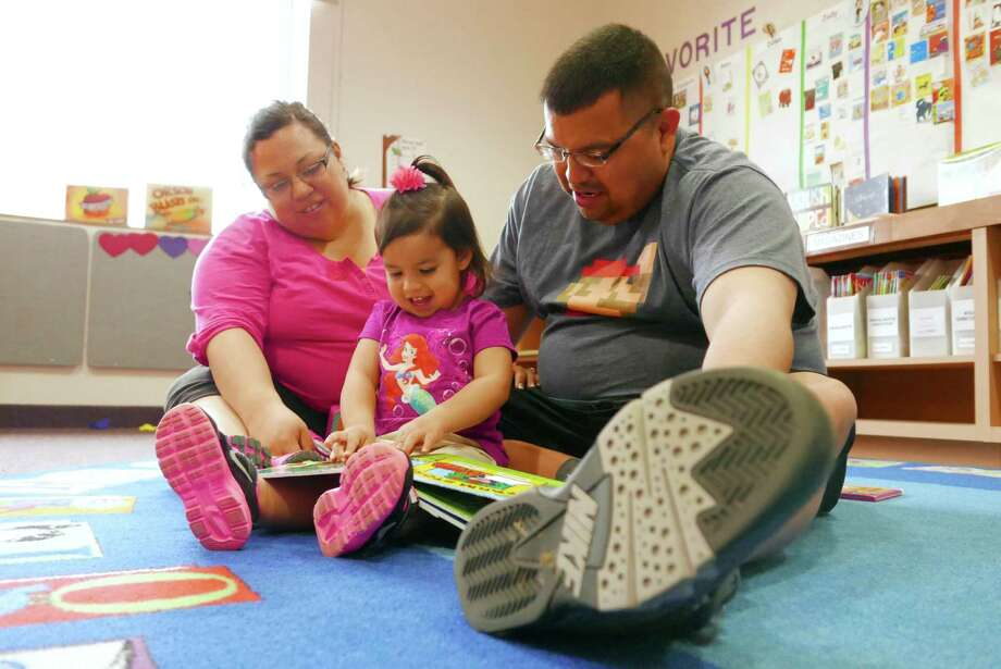 Emma Guzman, 2, reads a book with the help of her parents, Andrew and Jennifer Guzman, at the San Antonio Book Festival at the Southwest School of Art and the Central Library on April 11, 2015. The 2016 event will be April 6. Photo: Billy Calzada /San Antonio Express-News / San Antonio Express-News