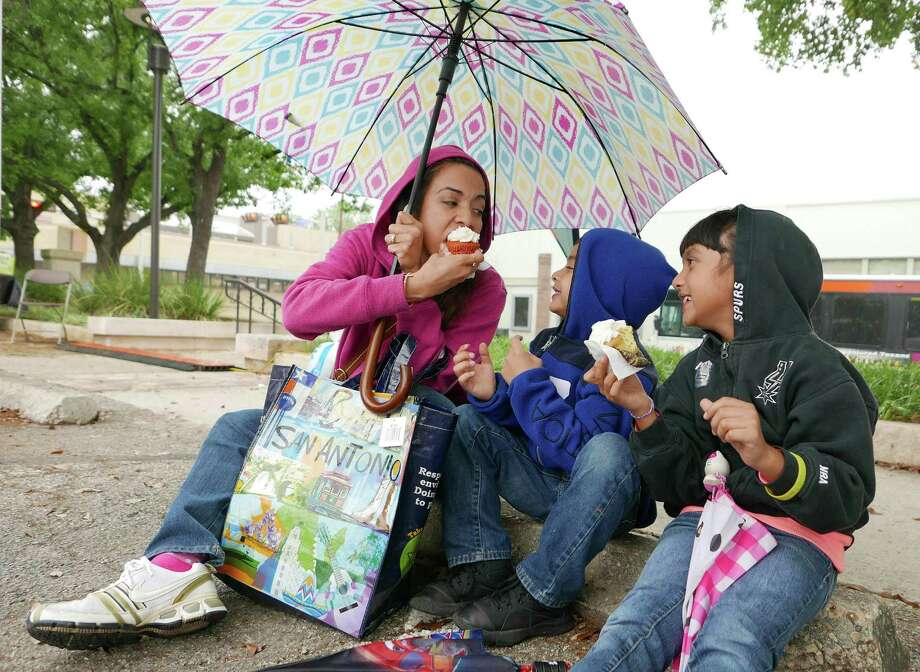 The rain doesn't faze Jacqueline Tovar and her children, Diego, 6, and Celeste, 9, at the San Antonio Book Festival. Photo: Billy Calzada /San Antonio Express-News / San Antonio Express-News