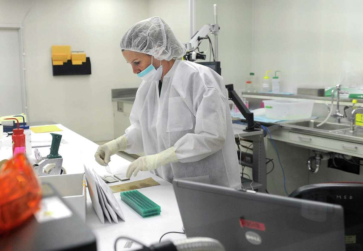 A forensic scientist prepares slides with DNA to be viewed under a microscope in the examination room at the State Police crime lab on Tuesday, Aug. 6, 2013 in Albany, N.Y. (Lori Van Buren / Times Union archive)