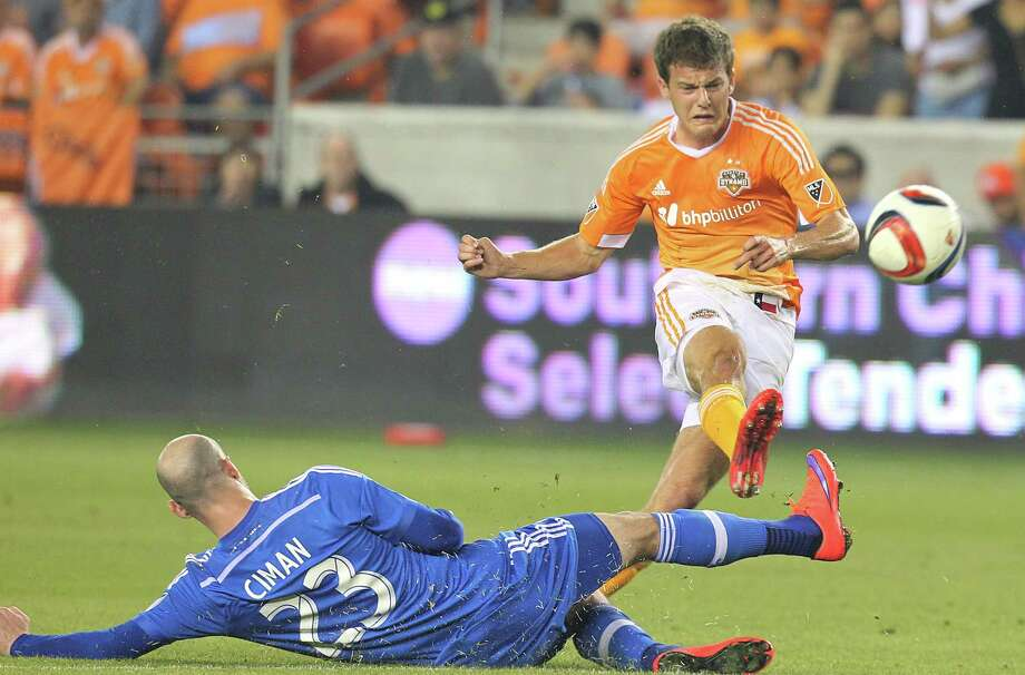 Dynamo midfielder Rob Lovejoy shoots past diving Montreal defender Laurent Ciman (23) to score Houston's third goal in the 80th minute in Saturday's 3-0 victory over the Impact at BBVA Compass Stadium. Photo: Thomas B. Shea, Freelance / © 2015 Thomas B. Shea