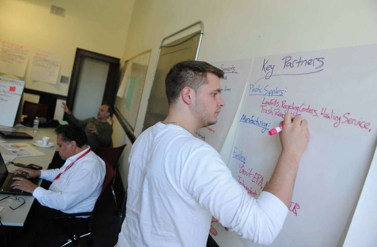 Team Precious Plastics member Zack Collado takes down note during Stamford Startup Weekend at the Stamford Innovation Center in Stamford, Conn. Sunday, April 12, 2015. Running from Friday evening through Sunday, ttendees voted on the best ideas for a new company and formed teams, attempting to hash out a business plan and in many cases a working prototype.