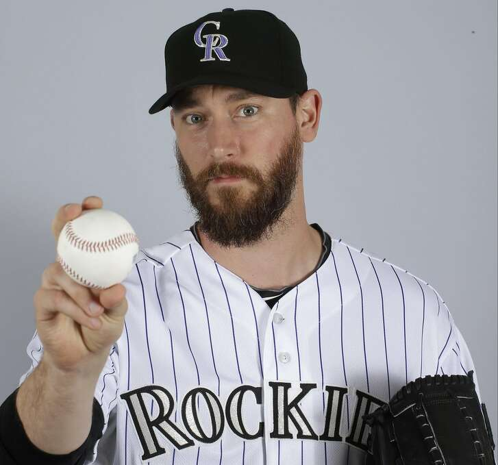 """FILE - In a March 2015 file photo, John Axford of the Colorado Rockies baseball team poses for a photo in Scottsdale, Ariz. Axford's 2-year-old son is improving following a rattlesnake bite. Jameson Axford remained hospitalized for an eighth straight day, but Axford said Wednesday, Apri his son was able to sleep through the night as he deals with pain. Doctors have saved his right foot, but there is fear one of his toes may need to be amputated. """"It's looking better,"""" Axford said. """"We're going by doctors' orders. They know more than we do. We're going to trust them to heal him the best way possible."""" (AP Photo/Darron Cummings, File)"""