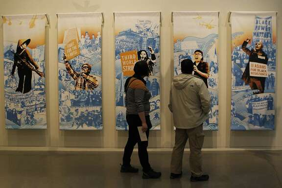 "Deanna Vecchiarelli (left) and Keith Lau observe a piece by Thomas Wong titled ""One Struggle, Many Fronts"" during the opening debut of the art exhibit ""Who is Oakland?"" at the Oakland Museum of California in Oakland, Calif. Sunday, April 12, 2015."