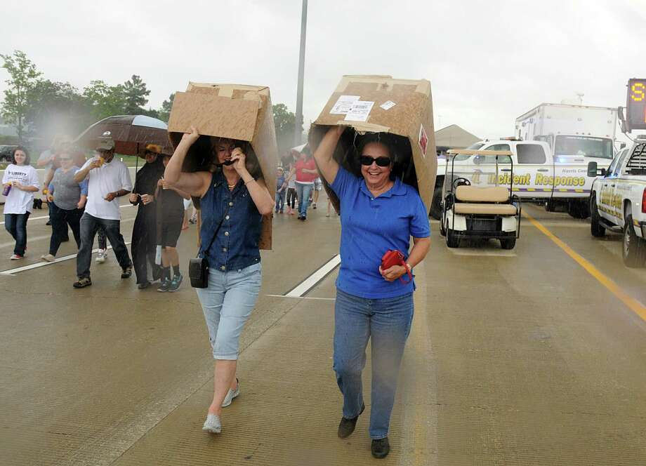 Janet Canton, of Magnolia, and Sandy Ferrell, of Tomball, use boxes as cover during a sudden rain shower during the Stroll the Toll event on the new Tomball Tollway. Participants were able to walk on the new tollway before it opened to automobiles at 6 p.m. on Sunday. Photo: David Hopper, For The Chronicle / freelance