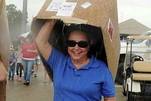 Janet Canton, of Magnolia, and Sandy Ferrell, of Tomball, use boxes as cover during a sudden rain shower during the Stroll the Toll event on the new Tomball Tollway. Participants were able to walk on the new tollway before it opened to automobiles at 6 p.m. on Sunday.