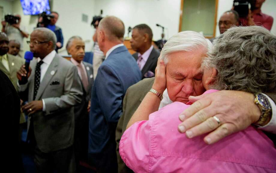 North Charleston Mayor Keith Summey, left, is embraced by Connie Rozycko during a service at Charity Missionary Baptist Church in the wake of the death of Walter Scott, the black driver who was fatally shot by a white police officer after he fled a traffic stop, Sunday, April 12, 2015, in North Charleston, S.C. The officer, Michael Thomas Slager, has been fired and charged with murder. (AP Photo/David Goldman) Photo: David Goldman, STF / AP
