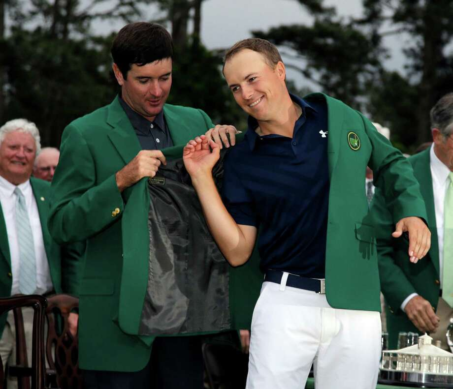 Bubba Watson, who won in 2014, gives Jordan Spieth a helping hand with the champion's traditional green jacket after the 21-year-old Texan became the Masters' first wire-to-wire winner since 1976 and tied the 72-hole scoring record of 18 under par. Photo: Matt Slocum, STF / AP