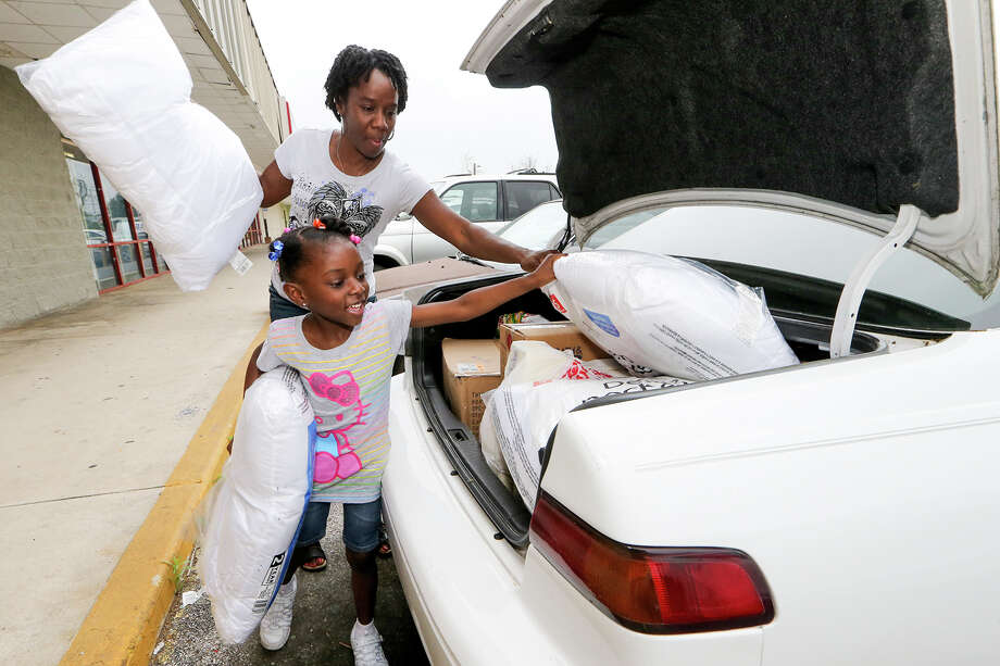 Layanna Banks, 5, and her mother, Veron Banks, unload pillows and other items from their car at the SAMM Ministries Donation Center, 5246 Blanco Rd, on Friday, April 3, 2015. Layanna saw the need to help homeless children and convinced her family to start a donation drive.  MARVIN PFEIFFER/ mpfeiffer@express-news.net Photo: Marvin Pfeiffer, Staff / San Antonio Express-News / Express-News 2015