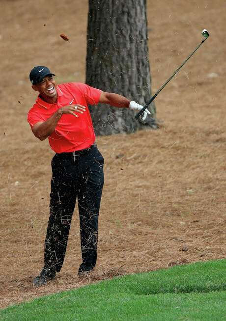 Tiger Woods feels the effects of hitting a tree root while trying to escape the pine straw on the ninth hole. Photo: David Cannon, Staff / 2015 Getty Images