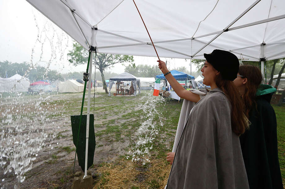 Alyssa Pfeiffer, 16, removes water pooling on the top of the tent at the San Antonio Highlands Games & Celtic Festival at the Helotes Fairgrounds, Sunday, April 12, 2015. The two day event featured food, exhibits and games. Photo: JERRY LARA, San Antonio Express-News / © 2015 San Antonio Express-News