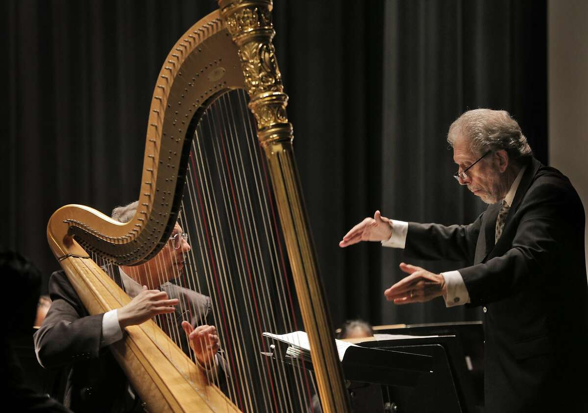 Conductor David Ramadanoff leads harpist Dan Levitan, left, during the final performance of the 2014-2015 season for the Vallejo Symphony Orchestra at Lander Hall on Mare Island in Vallejo, Calif., on Sunday, April 12, 2015. Vallejo Symphony is replacing its longtime conductor David Ramadanoff after 31 years as music director.