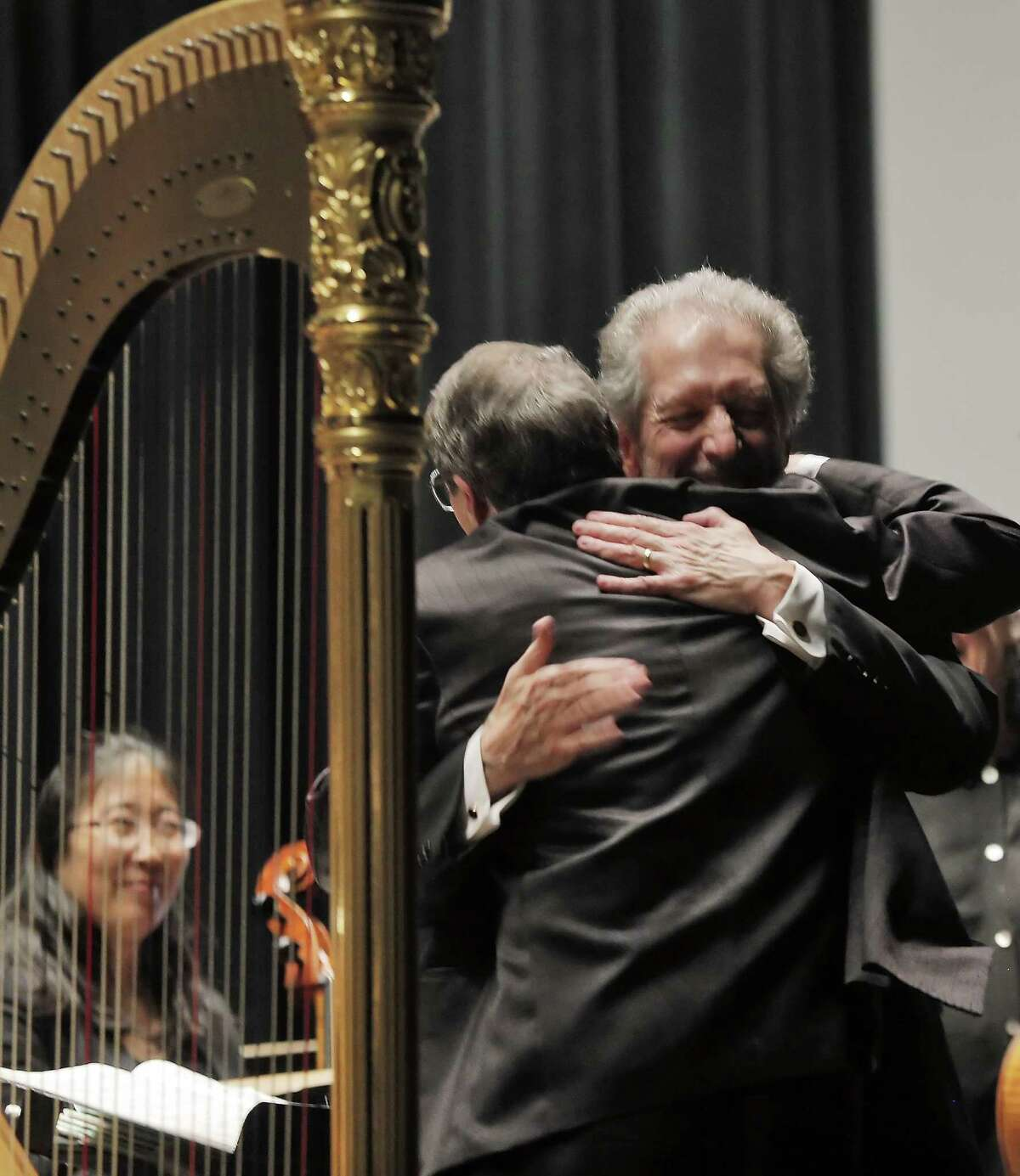 Conductor David Ramadanoff is hugged by harpist Dan Levitan, left, during the final performance of the 2014-2015 season for the Vallejo Symphony Orchestra at Lander Hall on Mare Island.