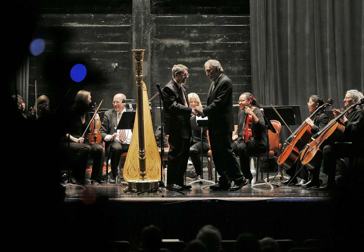 Conductor David Ramadanoff shakes hands with harpist Dan Levitan, left, during the final performance of the 2014-2015 season for the Vallejo Symphony Orchestra at Lander Hall on Mare Island in Vallejo, Calif., on Sunday, April 12, 2015. Vallejo Symphony is replacing its longtime conductor David Ramadanoff after 31 years as music director.