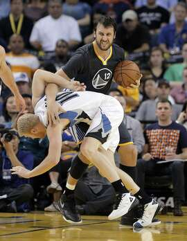 Andrew Bogut (12) tussles for a rebound after a collision with Chase Budinger (10) during the Golden State Warriors game against the Minnesota Timberwolves at Oracle Arena in Oakland, Calif., on  Saturday, April 11, 2015.