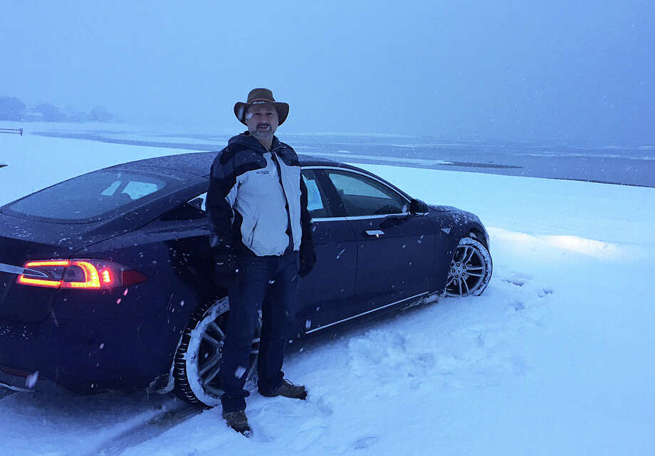 Snowy start: Westport resident Michael Staw about to leave town on the first day of his cross-country trip in a Tesla Model S electric car. Photo: Contributed Photo / Westport News