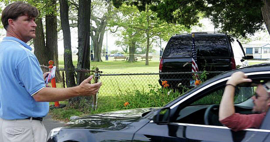 Stuart McCarthy, collecting tickets at the Compo Beach entrance before one of the town's annual July 4 fireworks shows over the shoreline, has announced plans to retire as parks and recreation director. Photo: File Photo / Westport News