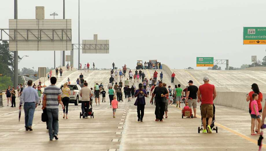 Participants stroll toward the Alice Road overpass during the Stroll the Toll event on the new Tomball Tollway. Participants were able to walk on the new tollway before it opens to automobiles at 6 p.m. on Sunday. Photograph by David Hopper Photo: David Hopper, Freelance / freelance