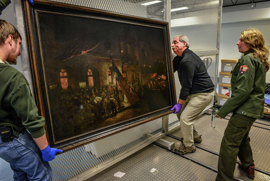 The National Park Service museum has a painting by an eyewitness of Lincoln being carried from Ford's Theater after being shot.  Pictured, from left, Lyndon Novotny, materials handler, Bob Sonderman, Director & regional curator, and Laura Anderson, National Park Service museum curator for the National Mall. Photo: Bill O'Leary, Washington Post / THE WASHINGTON POST