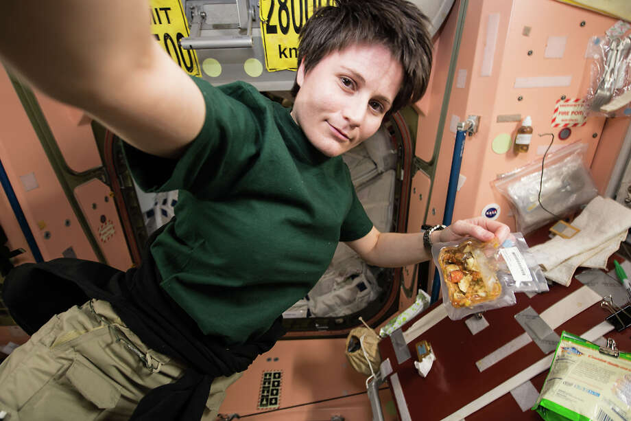 European Space Agency astronaut Samantha Cristoforetti prepares her dinner aboard the International Space Station, December 2014. If the SpaceX Dragon supply mission succeeds April 13, 2015, she will have an espresso machine. (NASA.gov)