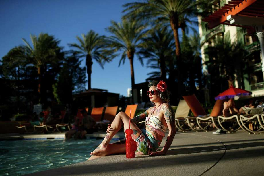 In this April 4, 2015, photo, a woman who goes by Martha War sits by the pool during the Viva Las Vegas Rockabilly Weekend in Las Vegas. Thousands of rockabilly fans attended the 18-year-old event. Photo: John Locher, AP / AP