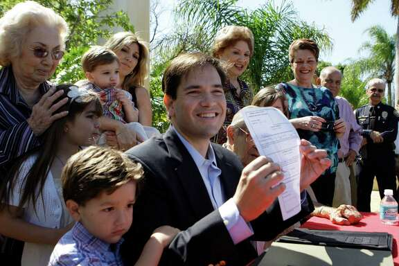 FILE - In this April 27, 2010 file photo, Marco Rubio, surrounded by family members, holds up a signed document declaring his candidacy in the Florida GOP primary for U.S. Senate in West Miami, Fla. Republicans are on offense in scores of House and Senate races nationwide as persistent economic woes and lukewarm support for President Barack Obama continue to weaken Democrats' hold on Congress. From left is his son Anthony, 4, mother Oria, daughter Daniella, 7, wife Jeanette, and son Dominick, 2.