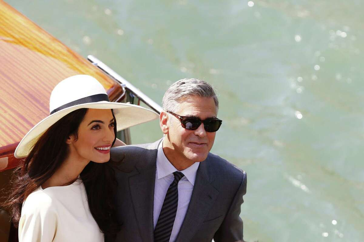 TOPSHOTS -- AFP PICTURES OF THE YEAR 2014 -- US actor George Clooney and British lawyer Amal Alamuddin leave the palazzo Ca Farsetti on a taxi boat on September 29, 2014 in Venice, after a civil ceremony to officialise their wedding. AFP PHOTO / PIERRE TEYSSOTPIERRE TEYSSOT/AFP/Getty Images ORG XMIT: MER2015041313471660