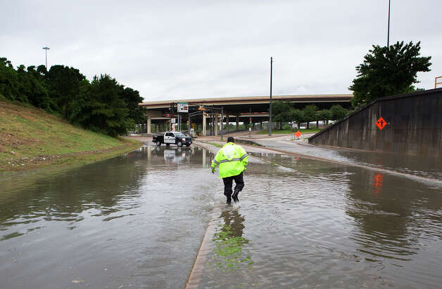 Travis Street and Interstate 45  A METRO officer walks in the flooded Travis St. entrance to I-45 Wednesday, May 28, 2014, in Houston. Authorities turned cars around and prohibited passage through the flooded area. Photo: Cody Duty, Houston Chronicle File / © 2014 Houston Chronicle