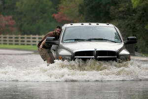 A man rides on the side of a truck in two feet of flood water on Longwood Trace Drive in the Longwood neighborhood as floodwaters from the Little Cypress Creek flowed over its banks Friday, July 13, 2012, in Cypress.
