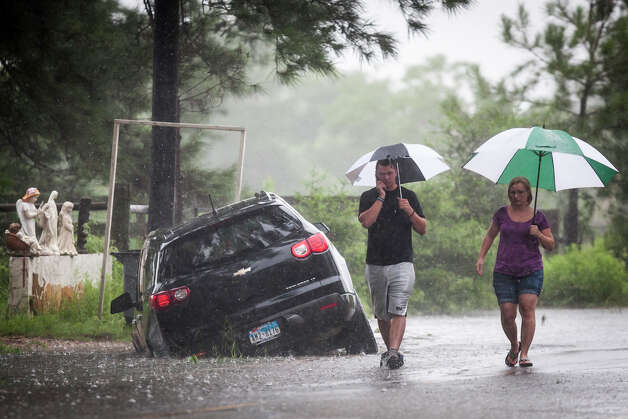 Telge Road near Spring Cypress Road  Raymond Valenta, left, and his mother Koran Kaptchinskie phone for help after their car was stranded in high water on Telge Rd. near Spring Cypress Rd. in northwest Houston, Thursday, July 12, 2012, in Houston. ( Michael Paulsen / Houston Chronicle ) Photo: Michael Paulsen, Houston Chronicle File / © 2012 Houston Chronicle