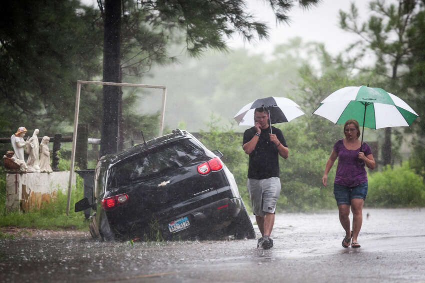 Telge Road near Spring Cypress Road Raymond Valenta, left, and his mother Koran Kaptchinskie phone for help after their car was stranded in high water on Telge Rd. near Spring Cypress Rd. in northwest Houston, Thursday, July 12, 2012, in Houston. ( Michael Paulsen / Houston Chronicle )