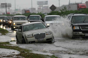 Vehicles move past a stalled car in the high water along the I-45 northbound feeder near Crosstimbers Thursday, Oct. 31, 2013, in Houston. ( Melissa Phillip / Houston Chronicle )