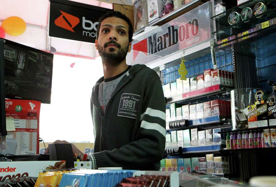 Cashier Imad Awad checks on customers at GSM/Fine Foods, Monday, April 13, 2015, in Berkeley, Calif. A proposed ordinance would ban the sale of tobacco products within 1,000 feet of schools or parks. The store is located near Berkeley High School and the ordinance could force the business to close as tobacco products are a large source of the store's income. Photo: Santiago Mejia / The Chronicle / ONLINE_YES