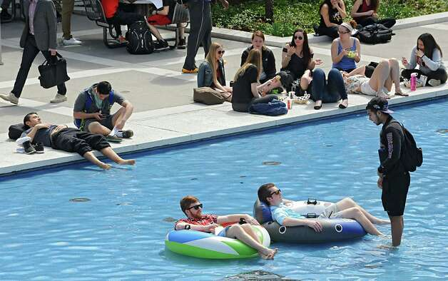 Students at the University at Albany enjoy the warm weather around the fountain including juniors Gingy Bennett, left, and Bill Grube both of Long Island who are taking to their friend Ricardo Gaitan of Westchester from their pool floats on Monday, April 13, 2015 in Albany, N.Y. (Lori Van Buren / Times Union) Photo: Lori Van Buren