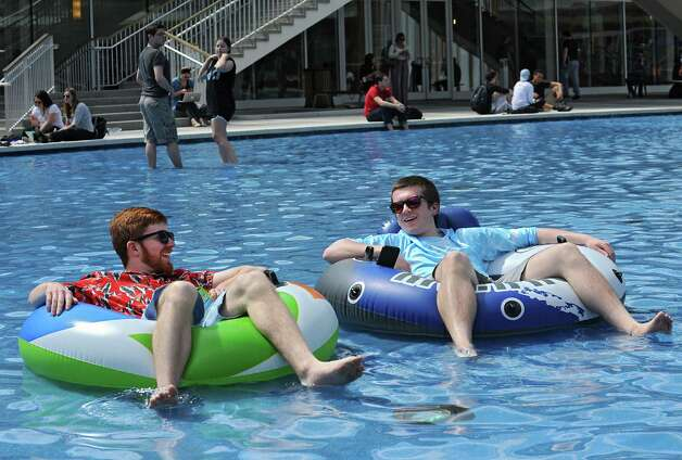 Students at the University at Albany enjoy the warm weather around the fountain including juniors Gingy Bennett, left, and Bill Grube both of Long Island who are taking in some vitamin D from their pool floats on Monday, April 13, 2015 in Albany, N.Y. (Lori Van Buren / Times Union) Photo: Lori Van Buren