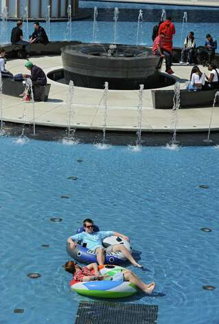 Students at the University at Albany enjoy the warm weather around the main fountain including juniors Gingy Bennett, bottom, and Bill Grube both of Long Island who are taking in some vitamin D from their pool floats on Monday, April 13, 2015 in Albany, N.Y. (Lori Van Buren / Times Union) Photo: Lori Van Buren