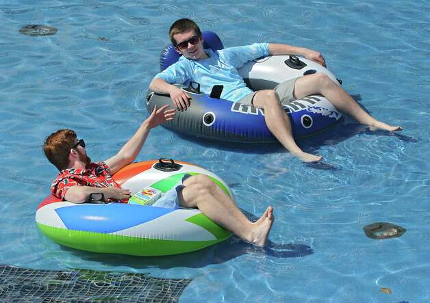 University at Albany juniors Gingy Bennett, left, and Bill Grube both of Long Island soak in some vitamin D from their pool floats in the main fountain on Monday, April 13, 2015 in Albany, N.Y. (Lori Van Buren / Times Union) Photo: Lori Van Buren