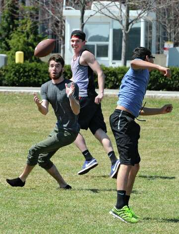 University at Albany student James Hartigan, left, intercepts a pass that was intended for Dennis Sosa, right, as Ryan Dowd watches in background during a pickup game of football in Collins Circle on Monday, April 13, 2015 in Albany, N.Y. (Lori Van Buren / Times Union) Photo: Lori Van Buren