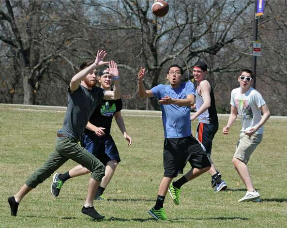 From left, University at Albany students James Hartigan, Collin O'Connor, Dennis Sosa, Ryan Dowd and James Canzoneri play a pickup game of football in Collins Circle on a beautiful spring day, Monday, April 13, 2015 in Albany, N.Y. (Lori Van Buren / Times Union) Photo: Lori Van Buren