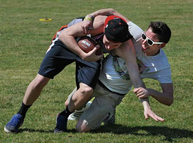 University at Albany student Ryan Dowd is tackled by James Canzoneri during a pickup game of football in Collins Circle on Monday, April 13, 2015 in Albany, N.Y. (Lori Van Buren / Times Union) Photo: Lori Van Buren