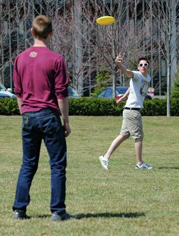 University at Albany students Ben Krish, left, and James Canzoneri toss a frisbee on a beautiful spring day in Collins Circle on Monday, April 13, 2015 in Albany, N.Y. (Lori Van Buren / Times Union) Photo: Lori Van Buren