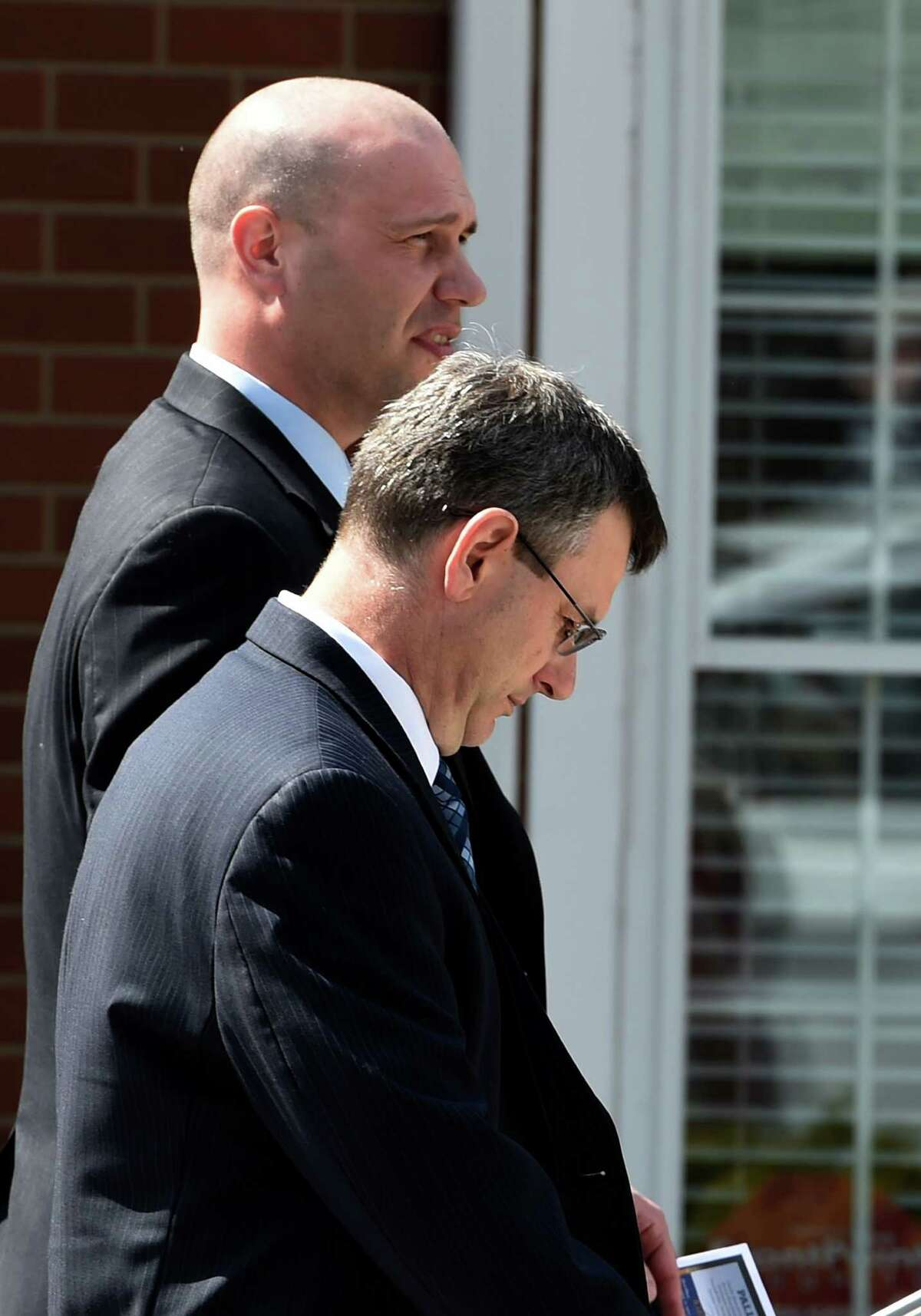 Acting Albany Police Chief Brendan Cox, foreground, leaves the Greater St. John's Church Monday morning April 13, 2015 in Albany, N.Y. after paying his respects to the family of Donald