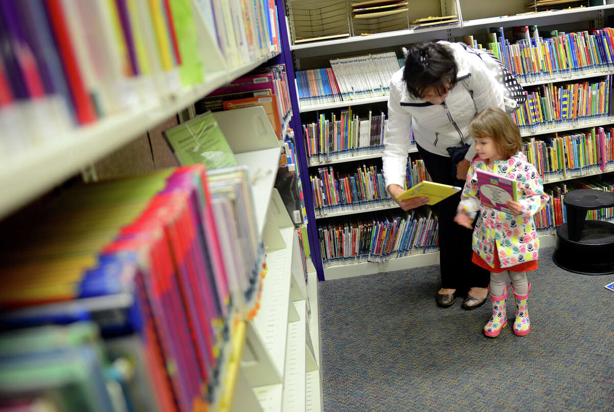 Fairfield resident Pat Grossarth hands a book to her grandchild Gabriella Rubio, 3, at the Stratford Library in Stratford, Conn., on Tuesday Apr. 7, 2015. On a regular basis, Grossarth drops off books she has borrowed from the Fairfield library here too.Gov. Dannel P. Malloy defended his proposed $3.5 million cut to the State Library system claiming that the lingering effects of the recession and constitutional limits on increased spending forced his proposed cut to Connecticard, the program that reimburses libraries for loaning books to out of towners.