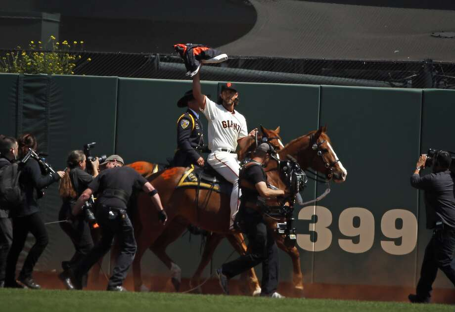 San Francisco Giants' Madison Bumgarner rides the 2014 World Series championship flag out to be raised before Giants play Colorado Rockies in home opener at AT&T Park in San Francisco, Calif., on Monday, April 13, 2015. Photo: Scott Strazzante, The Chronicle