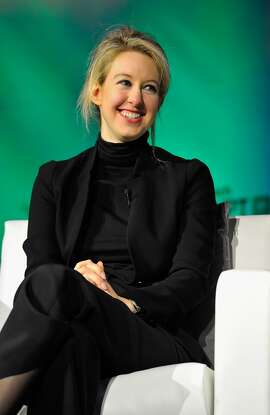 Theranos Chairman, CEO and founder Elizabeth Holmes has a work uniform of a black turtleneck with a black suit.