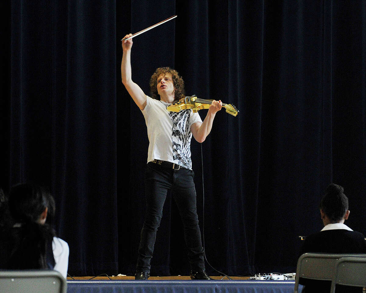 Alex Markov finishes a song on his electric violin during his visit to Waterside School in Stamford, Conn., on Monday, April 13, 2015. Markov was born in the Soviet Union and immigrated to Connecticut when he was very young.