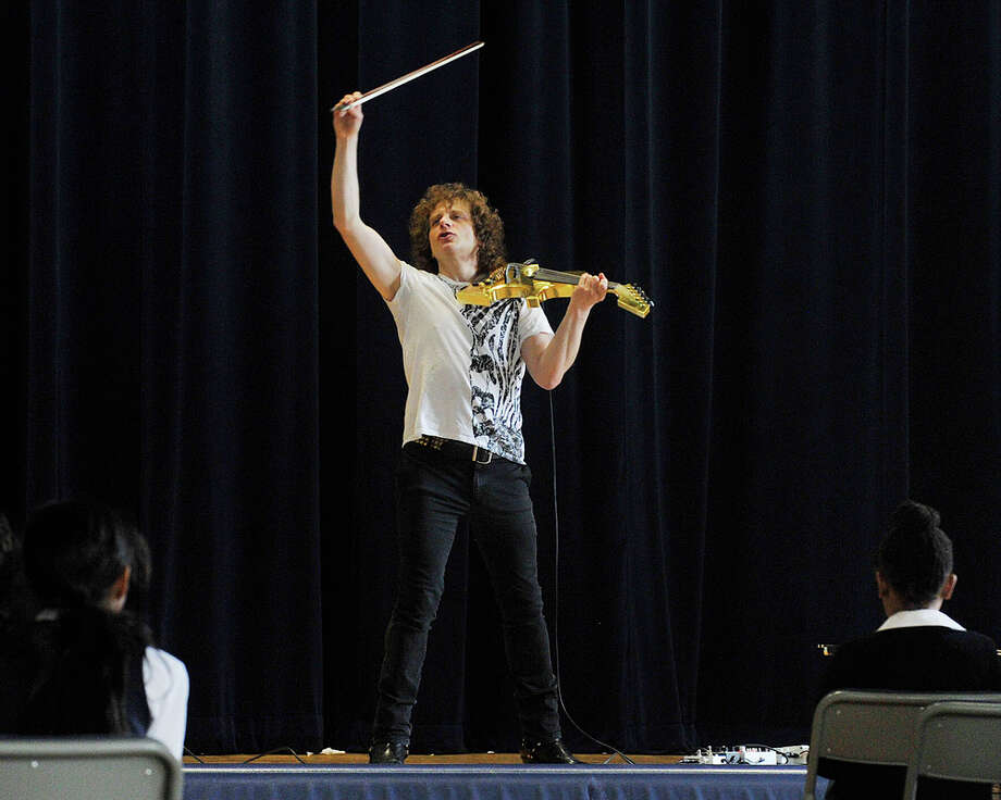 Alex Markov finishes a song on his electric violin during his visit to Waterside School in Stamford, Conn., on Monday, April 13, 2015. Markov was born in the Soviet Union and immigrated to Connecticut when he was very young. Photo: Jason Rearick / Stamford Advocate