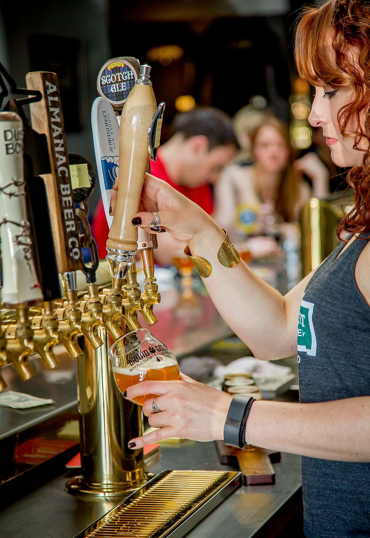 Bartender Kayleigh Bender pours a beer at Liquid Gold in San Francisco, Calif., on Sunday, April 12th, 2015.