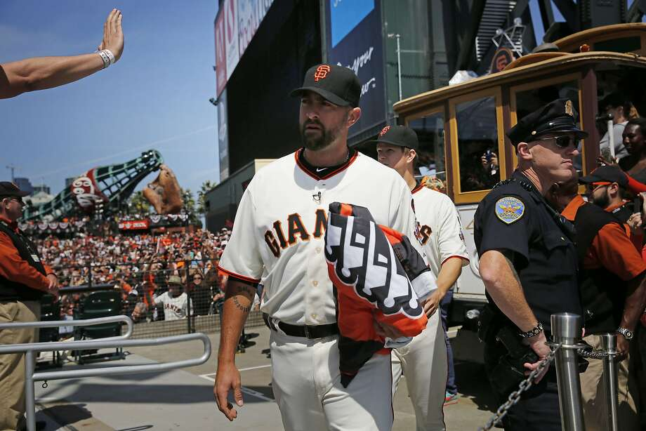 Giants pitcher Jeremy Affeldt (#41) carries the Championship flag to a flagpole above right field before the start of the home opener against the Colorado Rockies on Monday April 13, 2015 in San Francisco, Calif. Photo: Mike Kepka, The Chronicle